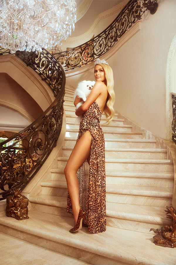 Paris Hilton wears a long leopard dress with a high slit of the boohoo x Paris Hilton Collection