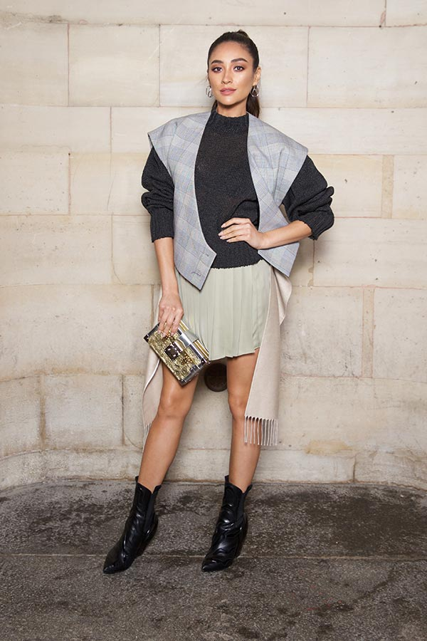 SHAY MITCHELL wears a geometrical vest, completed with cool boots and a sexy skirt