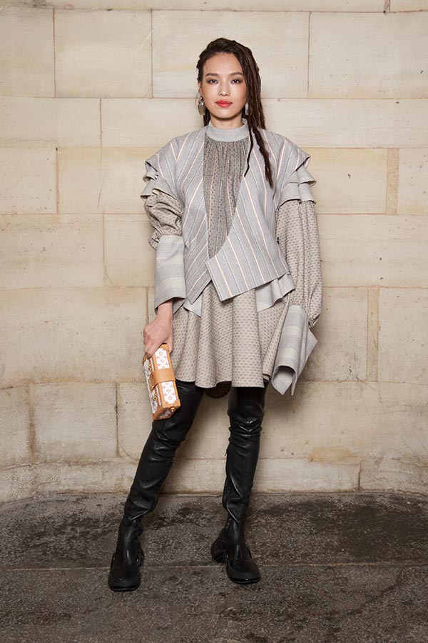 SHU QI wears an asymmetrical top and pleated skirt, completed with cool thigh-high-boots.