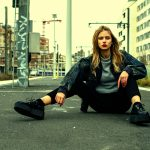 VALEUR MODEL Iona in an urban style sitting on the street