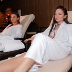 Valeur-Guide Belinda in the front with Emilie in the back, both are wearing bath robes and are relaxing on the loungers in the Club Olympus Spa at the Grand Hyatt.