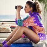 Iveta Mukuchyan is watching through a binoculars wearing a colorful sportive outfit