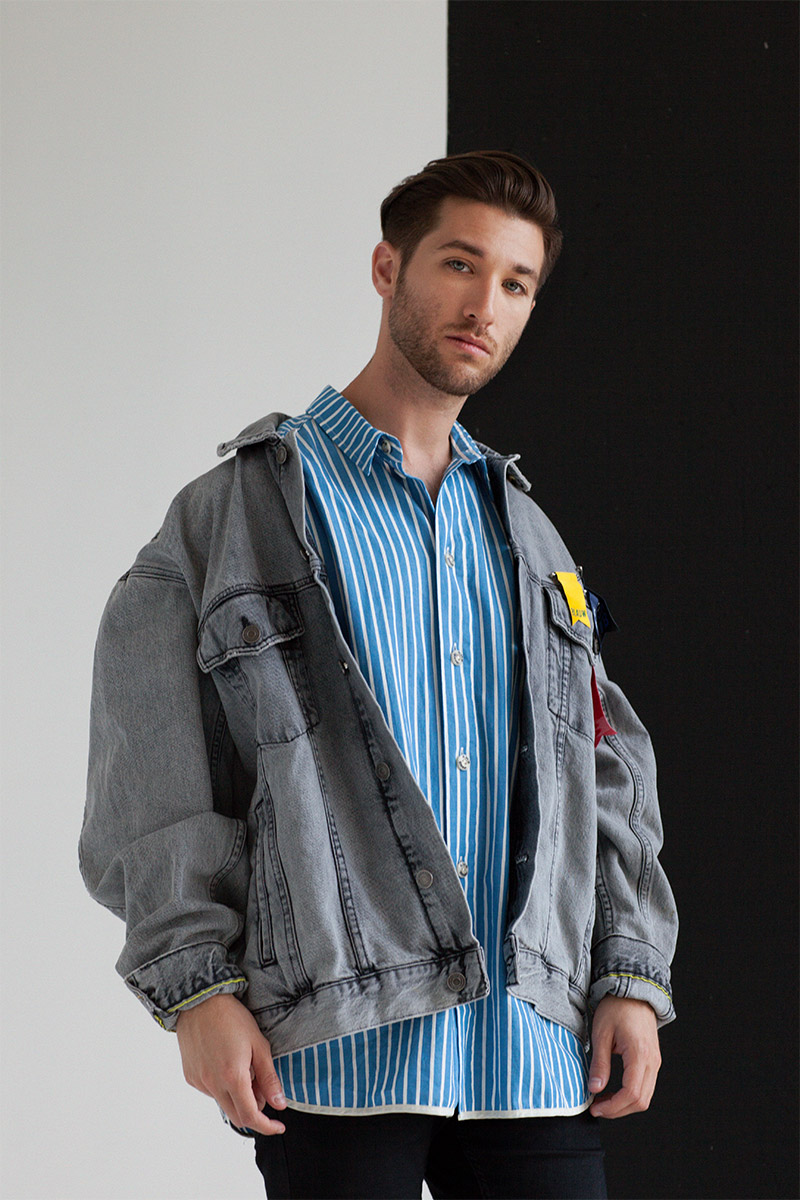 Justin Jesso standing in front of a black and white wall wearing a jacket over a blue-striped shirt
