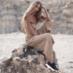 V-Guide Caro posing on a stone in a desert environment wearing a nude dress and black trainers